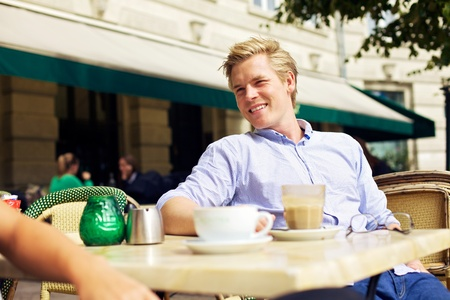 open air: Handsome guy hanging out and relaxing in an outdoor cafe Stock Photo