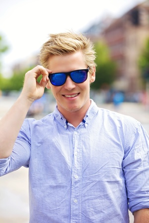 mens fashion: Portrait of a handsome and cool guy outdoors with his shades on