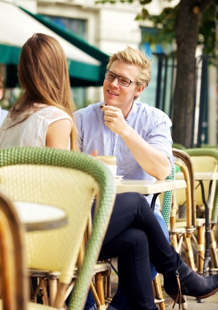 sidewalk talk: Cute guy listening to his girlfriend in a sunny open air cafe Stock Photo