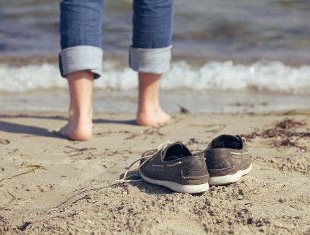 Man leaving his shoes behind to walk toward the water photo