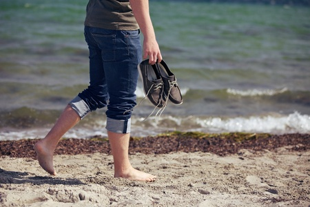 Barefoot man carrying his shoes walking along the sandy shoreline photo
