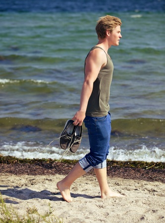 Handsome man carrying his shoes and walking alone on the beach photo