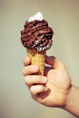 Closeup of a hand holding an ice cream in chocolate flavor photo