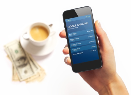 mobile commerce: Smartphone with bank information on screen and coffee and dollar bills on the background