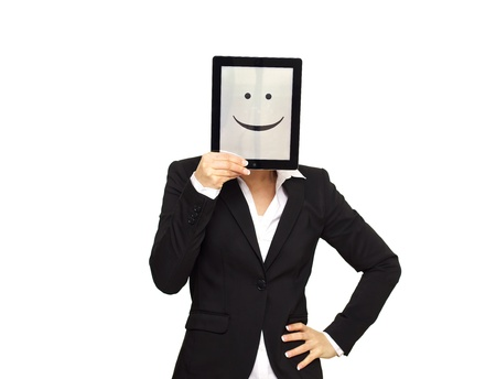 covering the face: Business woman hiding behind a digital tablet with a happy smiley face. Stock Photo
