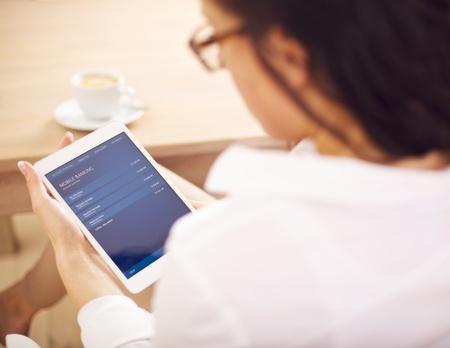 cuenta bancaria: Empresaria verificar su cuenta bancaria en l�nea usando su tableta digital