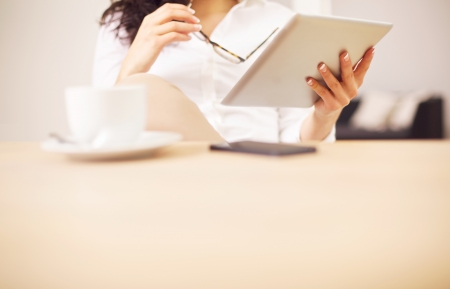 administrativo: Mesa de conferencia con una mujer que lee algo sobre su tableta digital