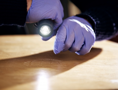 investigating: Hand holding a flashlight and searching for evidence
