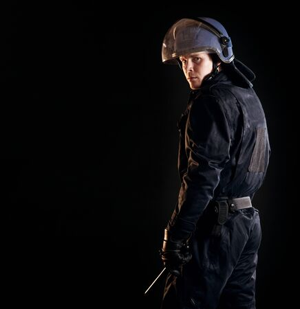 security laws: Portrait of a serious riot policeman isolated on black Stock Photo