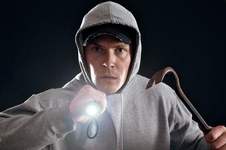 Burglar with crowbar and a flashlight ready for work Stock Photo - 17724756