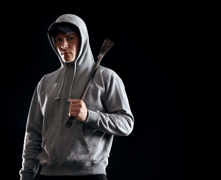 outlaw: Young outlaw holding a crowbar alone in the dark Stock Photo