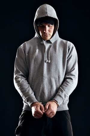 felon: Handcuffed offender wearing a hooded sweatshirt Stock Photo