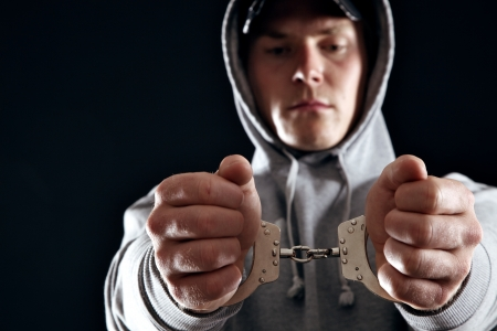 Gangster in handcuffs isolated in black background photo