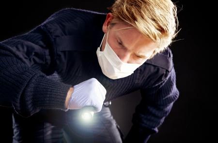 taschenlampe: Investigator h�lt eine Taschenlampe auf der Suche nach Beweisen