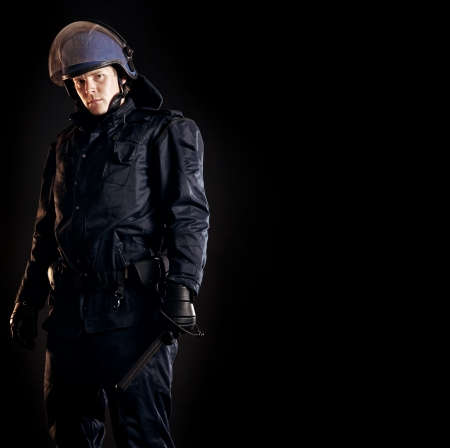 riot: Law enforcer in protective uniform ready for crowd control isolated on black Stock Photo