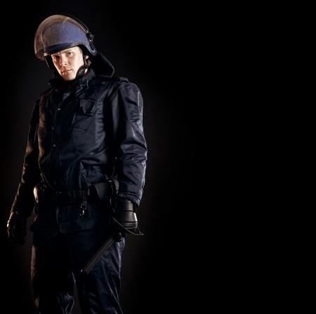 Law Enforcer in Schutz Uniform bereit für crowd control isoliert auf schwarz Standard-Bild