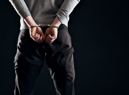 Murderer locked in handcuffs isolated on black photo
