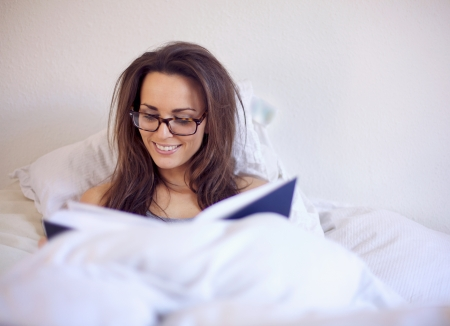 woman night: Woman reading a good book while on her bed