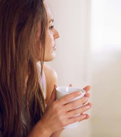 pensive woman: Pensive woman  in a quiet mood thinking of something over a cup of coffee Stock Photo