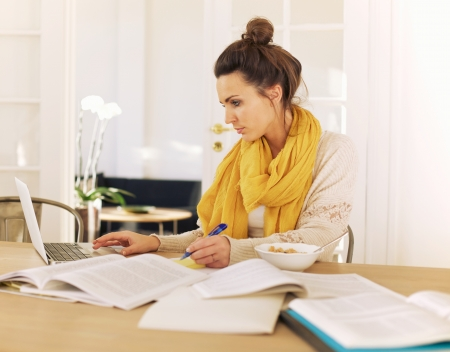 Young university student using laptop and books in studying at home Stock Photo