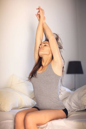 Sexy woman sitting on top of her bed doing early morning stretching photo