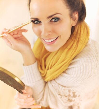Happy and confident woman putting makeup on photo