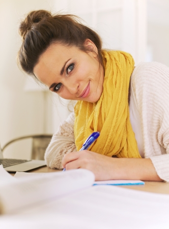 Closeup of a beautiful smiling woman looking at camera while writing on her notepad photo