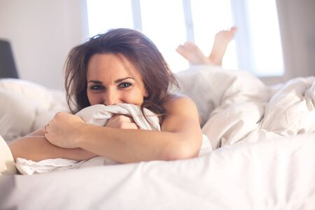 Cheerful woman indoor lying on her bed having fun photo