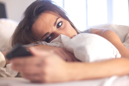 Woman lying on bed alone checking her phone for new text message photo