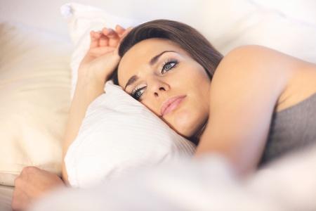 mujer pensativa: Primer plano de una mujer pensativa tendido en la cama descansando