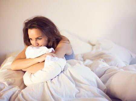 Pensive woman smiling and sitting alone on bed thinking of someone photo