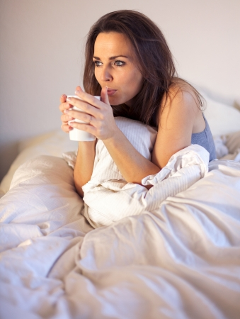 Woman sipping her coffee while still sitting on her comfortable bed photo