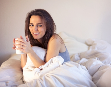 Cheerful woman sitting on top of bed enjoying her drink photo