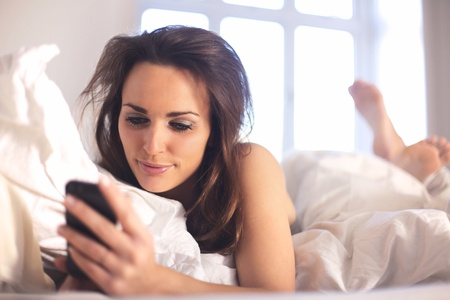 Relaxed woman at home reading a text message in her bright bedroom photo