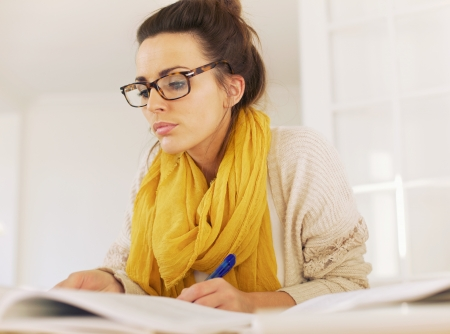Busy woman reading her textbook and taking down notes photo