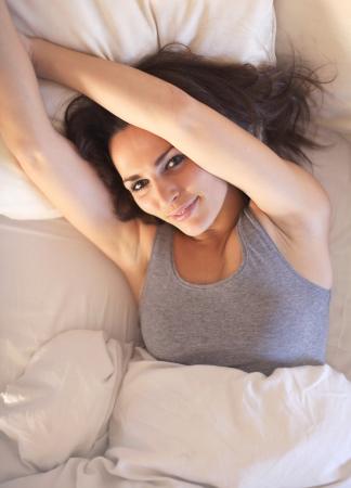 Lazy morning woman lying on bed stretching her arms Stock Photo - 18522171