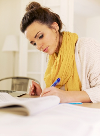 research education: Indoor woman busy writing something and studying all her books Stock Photo