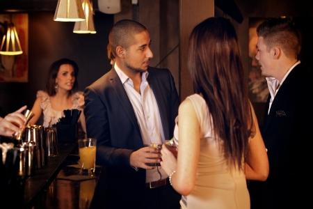socializando: Joven empresario pasar el rato y hablar con los amigos en el bar
