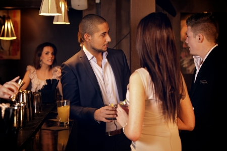 Young businessman hanging out and talking with friends at the bar photo