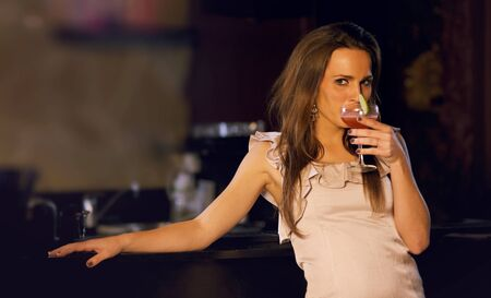 Sensual woman on the bars counter sipping wine Stock Photo