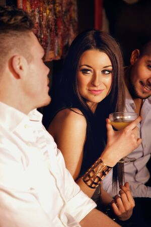 socialize: Stunning woman with drinks enjoying the party with male friends