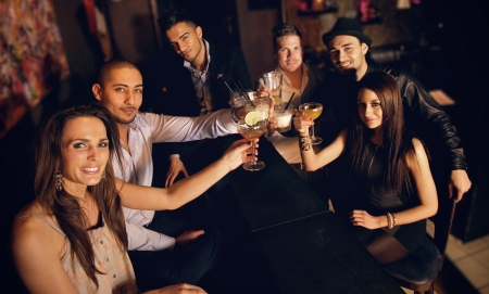 taverns: Group of friends at the bar raising their glass for a toast