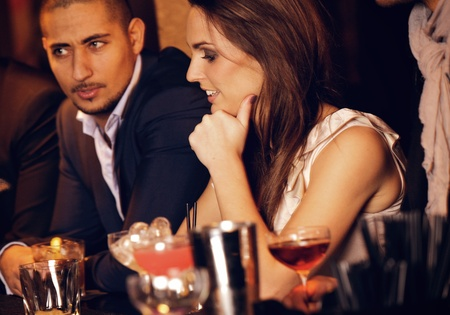 cocktail bar: Gorgeous woman sitting at the bar with her handsome boyfriend Stock Photo