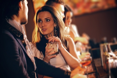 people partying: Young woman with a glass of wine talking to a man at the bar Stock Photo