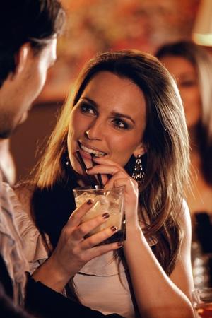 coquetear: Primer plano de una hermosa mujer en el bar hablando con un chico Foto de archivo