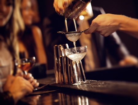 horizontal bar: Barman pouring wine from shaker and serving it Stock Photo