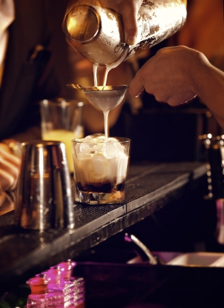 barman: Cold cocktail drink being prepared  by the bartender