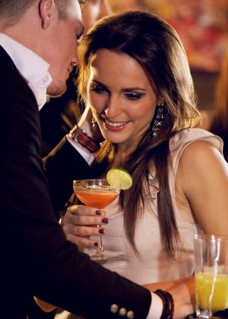 romantic dinner: Femme d'écoute comme ami chuchote son quelque chose de romantique à son Banque d'images