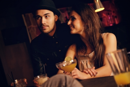 dining out: Young couple enjoying their date at the bar with their friends Stock Photo