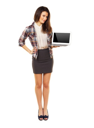 Full length woman in a studio showing copyspace on laptop photo